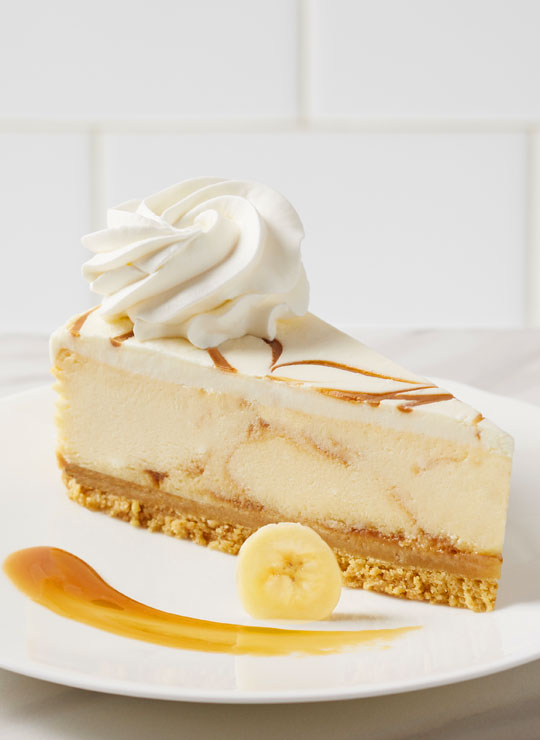 A slice of Bananas Foster Cheesecake, garnished with a banana and caramel