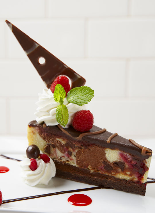 A slice of Chocolate Raspberry Cheesecake made with Ghirardelli®