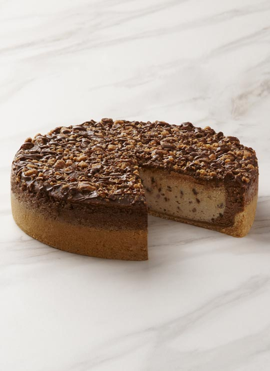 A slice of Reese's Peanut Butter Cheesecake, garnished with a mini Reese's Peanut Butter Cup